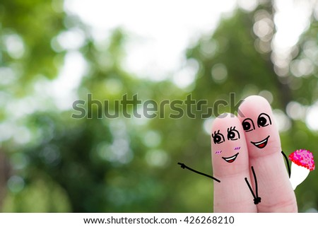 Finger art of a Happy couple. A man and a woman hug with pink hearts in the eyes.funny-finger-people -couple-smiling - stock photo