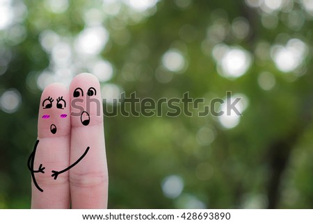 Finger art of a Happy couple.Happy pregnant woman and her husband in the park.A happy couple in love with painted smiley and hugging.Finger couple embracing with a blue sky background.fingers in love - stock photo
