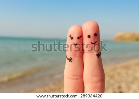 Finger art of a Happy couple. Man and woman have a rest on the beach sea. Man and woman hug on the background sea.  - stock photo