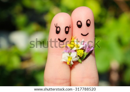 Finger art of a Happy couple. Man is giving flowers to a woman.  - stock photo