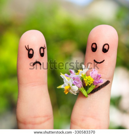 Finger art of couple. Man gives a woman a bouquet of flowers, she is not satisfied.  - stock photo