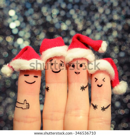 Finger art of friends celebrates Christmas. The concept of a group of people laughing in new year hats. Toned image.  - stock photo