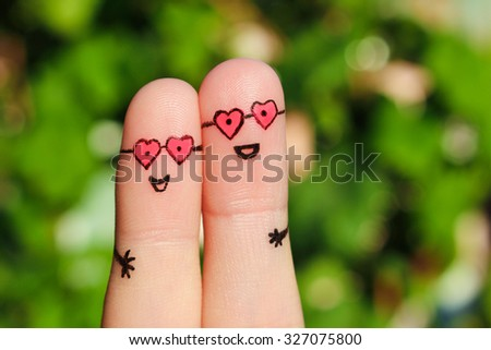 Finger art of Happy couple. Man and woman hug in pink glasses in shape of hearts. Concept of love at first sight. - stock photo