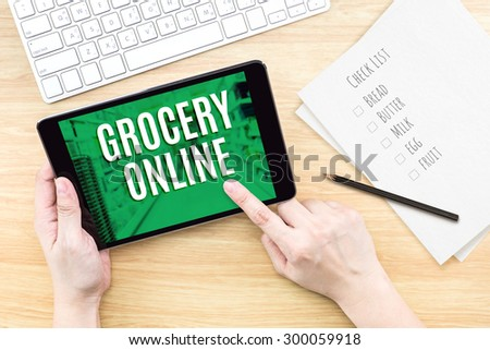 Finger click screen with Grocery online word with keyboard on wooden table,Digital Marketing concept. - stock photo