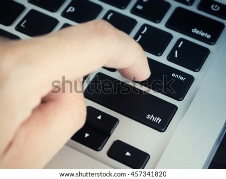 "Finger clicking ""Enter button"" on laptop keyboard - stock photo"