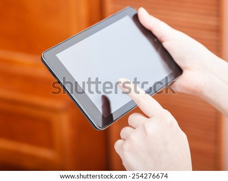 finger clicking tablet pc screen in office - stock photo