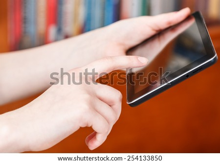 finger clicking touchpad screen in library room - stock photo