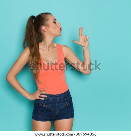 Finger Gun. Beautiful young woman blows into the barrel of a finger gun. Three quarter length studio shot on teal background. - stock photo