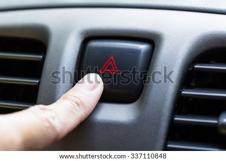 finger hitting car emergency light botton, man pressing red triangle car hazard warning button - stock photo