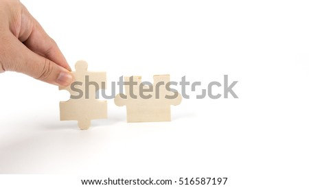 Finger holding pieces of blank wooden puzzle. Isolated on white background. Slightly de-focused and close-up shot. Copy space.