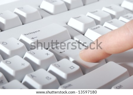 Finger is pressing the Enter on a keyboard. - stock photo