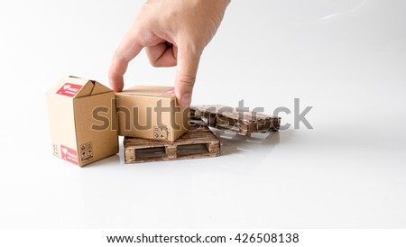 Finger lifting miniature cardbox with Fragile symbol on wooden pallet. Concept of handle with care or courier business. Isolated on white background. Slightly de-focused and close-up shot. Copy space. - stock photo