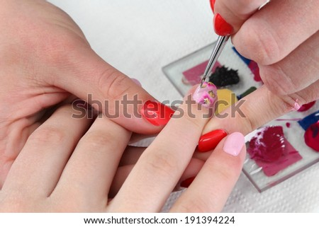 Finger nail treatment, painting flower with brush and lacquer