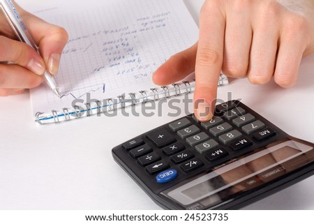 finger of girl presses on button of  black calculator on white table - stock photo
