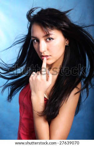Finger on the lips of a model. Hair motion. Portrait - stock photo