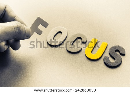 Finger pick a wood letters of Focus word - stock photo