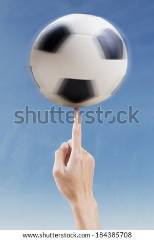 Finger playing with a soccer ball under blue sky - stock photo