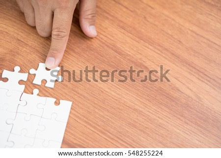 Finger point holding connecting piece jigsaw puzzle, Business connection, success and strategy concept.
