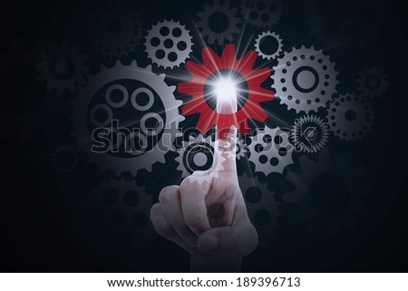 Finger pressing a cog gear symbolizing business control