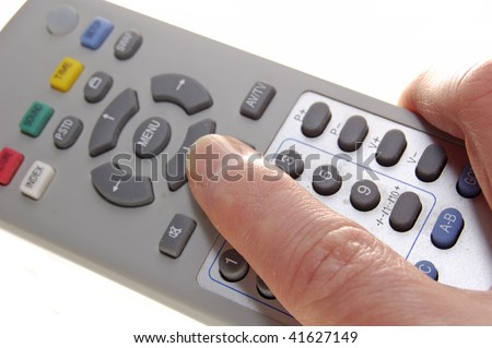 Finger pressing button on television remote control handset
