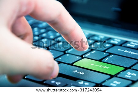 Finger pressing enter key close up - stock photo
