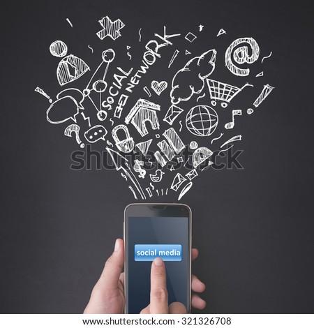Finger pressing social media button on smartphone on chalkboard background - stock photo