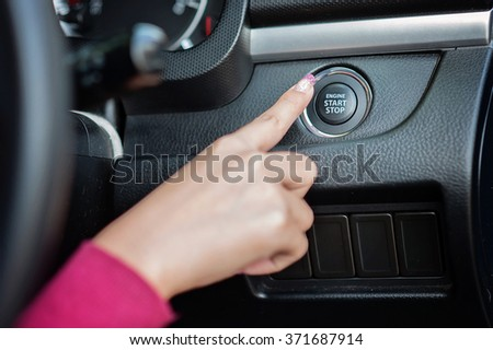 finger pressing the Engine start stop button of a car. /Focus selection