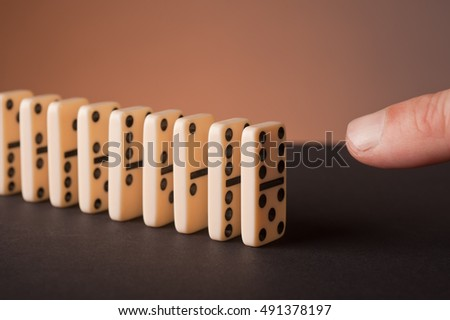 Finger pushing dominoes in a row