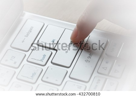 Finger pushing enter button on laptop keyboard. Close-up of typing male hands on keyboard. - stock photo
