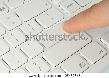 Finger pushing the button of keyboard - stock photo