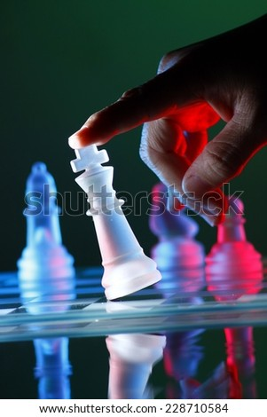 Finger tilting a chess piece on Chess Board Photo of a Finger tilting a chess piece on Chess Board - stock photo