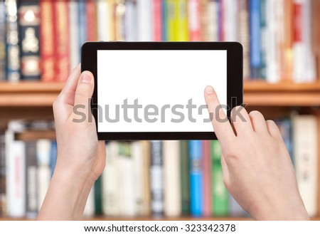 finger touches tablet pc screen with cut out screen on front of bookcase - stock photo