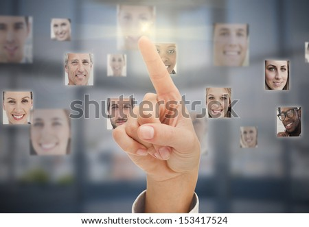 Finger touching futuristic interface showing human faces - stock photo