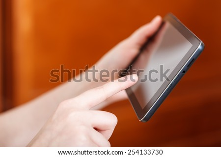 finger touching tablet pc screen in office - stock photo