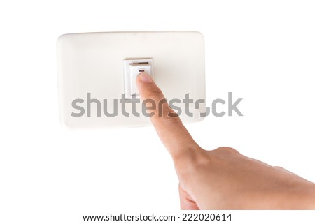 Finger turning white light switch on or off - stock photo
