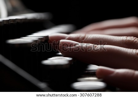 finger writing on old typewriter over wooden table background - stock photo