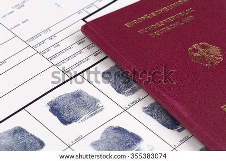 Fingerprint card with german travel passport - stock photo