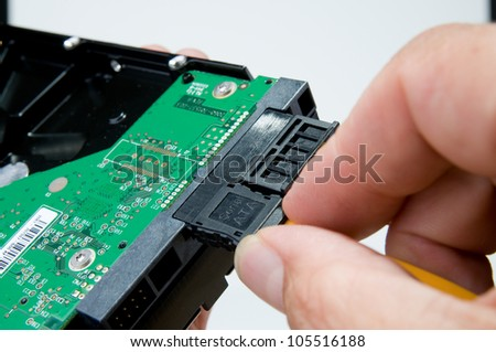 Fingers connecting serial ATA cable to a hard drive - stock photo