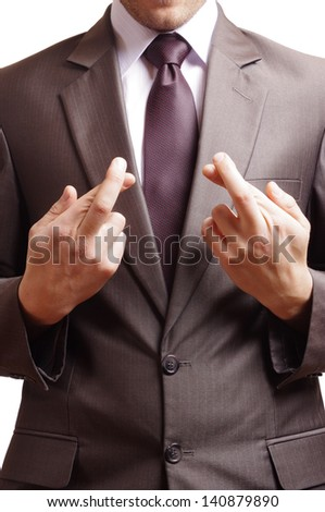 fingers crossed at the front of a suited man - stock photo
