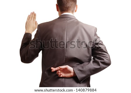 fingers crossed behind a suited backside and one arm raised - stock photo