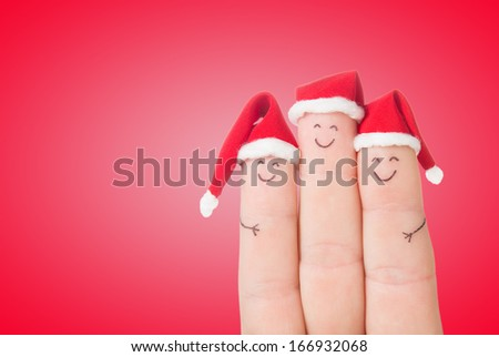 Fingers faces in Santa hats. Happy family celebrating concept for Christmas day. - stock photo