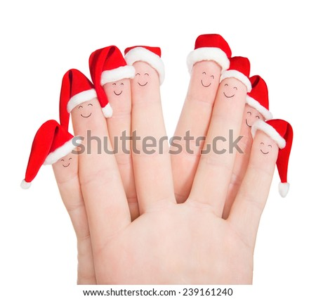 Fingers faces in Santa hats isolated against white background. Happy friends or family celebrating holiday concept for Christmas or New Years day