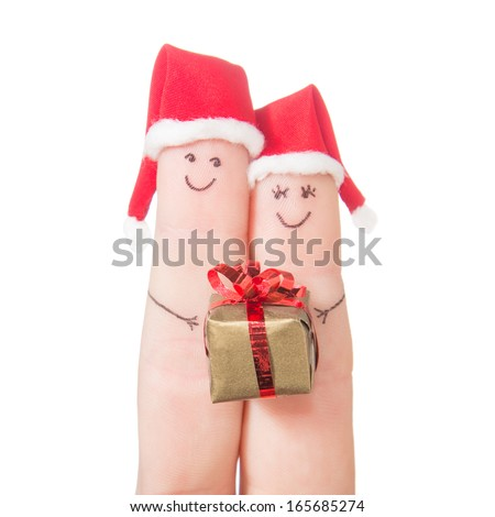 Fingers faces in Santa hats  with gift box isolated on white background. Happy couple celebrating concept for Christmas day. - stock photo