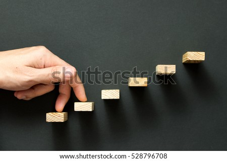 Fingers going up wooden stairway over black background