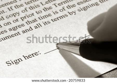 Fingers holding an ink pen and signing a contract document on the sign here signature line