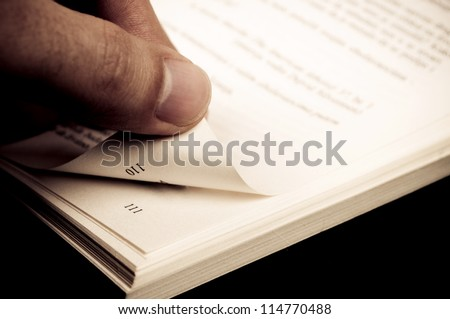 Fingers holding corner of the book page and turning new page - stock photo
