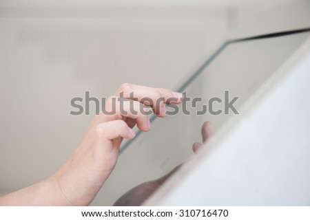 fingers of a young girl on the touchpad. Use in the banking sector