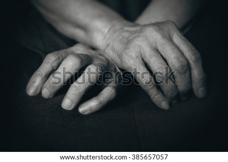 Fingers of the old man's hands in his lap