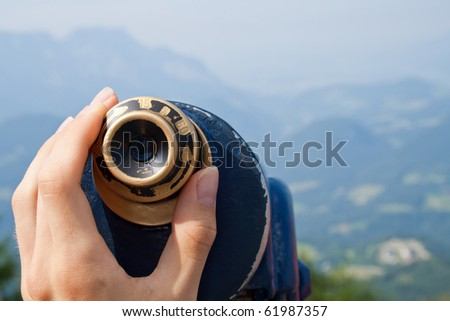 Fingers on an ocular of telescope. View on a valley and mountains. - stock photo