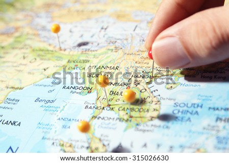 Fingers placing pin on Hanoi city on map - stock photo
